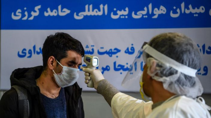 Boy in Afghanistan gets his temperature check