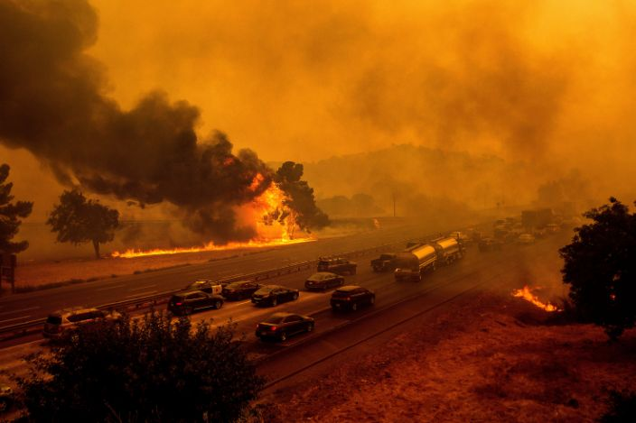 Flames from the LNU Lightning Complex fires jump Interstate 80 in Vacaville, Calif., Wednesday, Aug. 19, 2020. The highway was closed in both directions shortly afterward. Fire crews across the region scrambled to contain dozens of wildfires sparked by lightning strikes as a statewide heat wave continues.