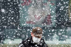 Man wearing mask and hat in snow