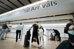 Passengers standing around and walking with suitcases in London's Heathrow airport