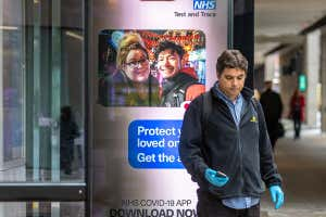 A man stands next to an NHS Test and Trace advertising board in Westminster