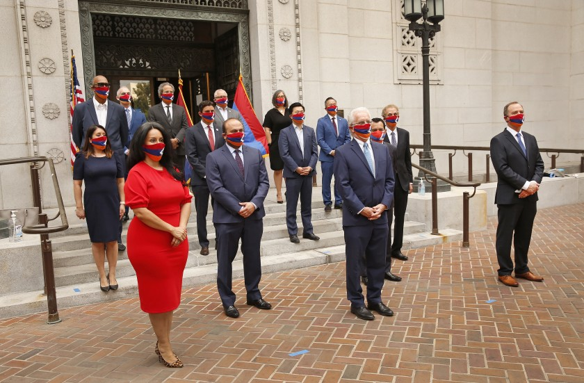 Local officials stand in masks and hold a flag outside L.A. City Hall