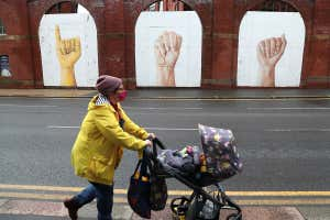 A woman pushing a baby stroller walks on a street during stricter restrictions due to the coronavirus outbreak in Sheffield, UK