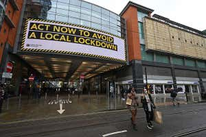 "Shoppers wearing face coverings pass beneath an electronic sign reminding pedestrians to ""act now to avoid a local lockdown"" in Manchester, UK"