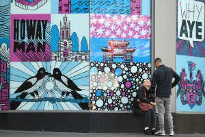 Two people face each other, one sitting and one standing, near artwork in Newcastle city centre, north-east England