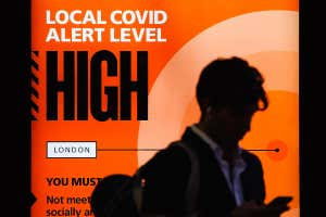 A government notice reminds people of 'high' or 'tier 2' coronavirus restrictions in London, UK