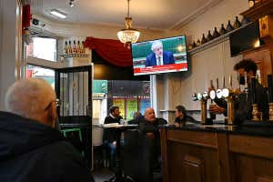 A television shows Britain's Prime Minister Boris Johnson speaking in the House of Commons in London, as customers sit at tables inside the Richmond Pub in Liverpool, north west England on October 12, 2020