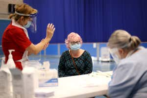 Two health workers speak with a woman before conducting a test for the coronavirus in Stoke-on-Trent, UK