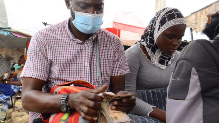 A man in Nigeria counting naira notes