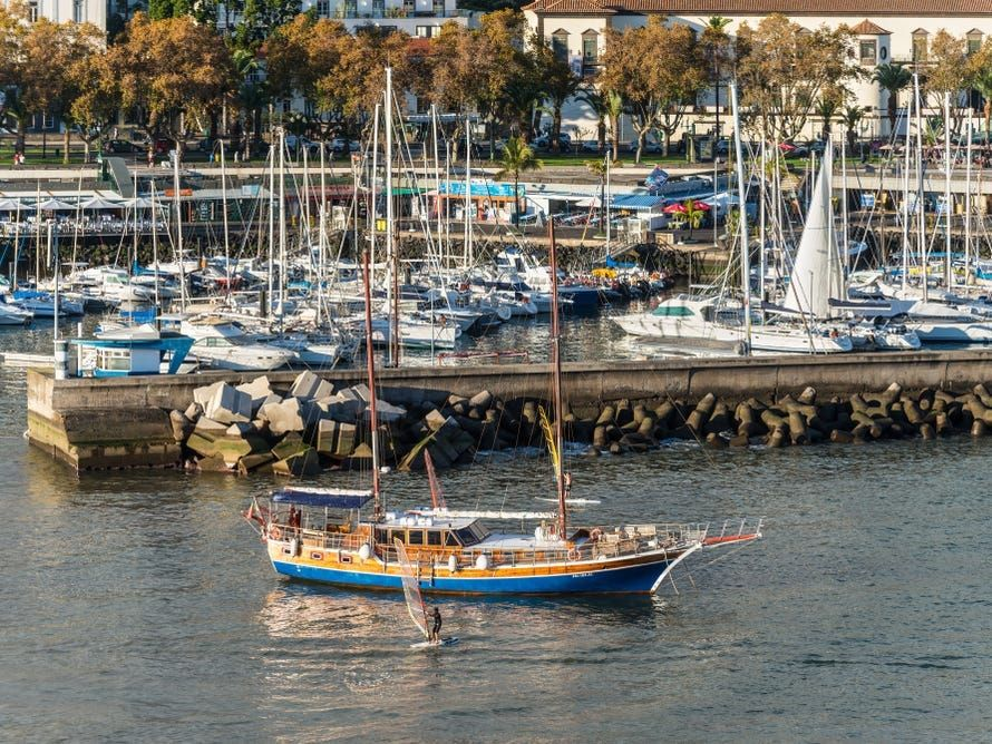 Funchal with a ship, yachts, boats and windsurfer in the harbor of Madeira Island, Portugal.ck_1067650190