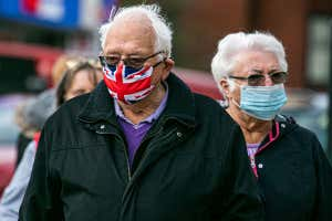 man and woman wearing Union Flag face masks