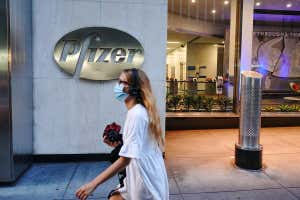 A person wearing a mask walking in front of Pfizer World Headquarters in New York City