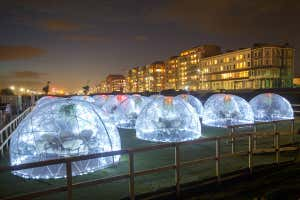 Lit-up pods, each catering for up to six people, at the Rockwater Igloo Village bar and restaurant in Hove, UK