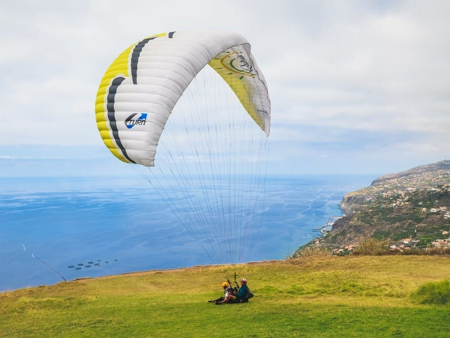 Arco da Calheta, Madeira, Portugal - Sep 16, 2019: Tandem paragliders landing on a grass on the cliffs above the Atlantic ocean. Madeiran landscape in background. Paragliding, active vacation.