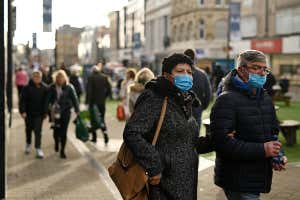 A man and a woman, both wearing face masks, walk with their arms linked in Leeds, UK