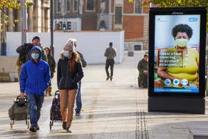 People wearing face coverings walk along a shopping street in Hull city centre in England