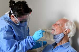 A nurse wearing personal protective equipment performs a coronavirus nose swab test on a participant in the Moderna covid-19 vaccine study in Miami