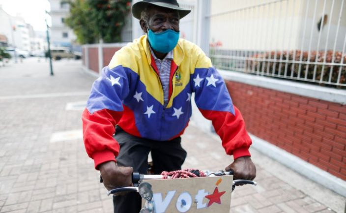 """A pro-government supporter dressed in a Venezuelan flag jacket cycles through the city with a sign that reads """"VOTA"""""""