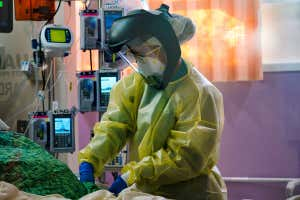 A nurse wearing personal protective equipment, including a face shield, cares for a patient at Scripps Mercy Hospital in Chula Vista, California