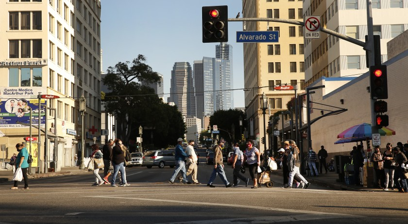 People cross a city street with skyscrapers in the background