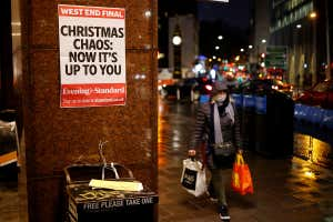 "A shopper walks past an Evening Standard newspaper stand in central London on 16 December, as new guidance on Christmas during the coronavirus pandemic was announced by the government. A poster advertising the newspaper stand reads: ""Christmas chaos: now it's up to you"""