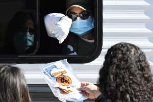 A Community Organized Relief Effort worker hands a coronavirus test kit to two women, at a walk-up covid-19 testing site in Los Angeles, California on 1 December