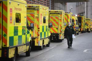A healthcare worker walks past a line of ambulances at the Royal London Hospital in London, UK