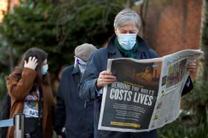 A man reads a newspaper as he waits in a queue
