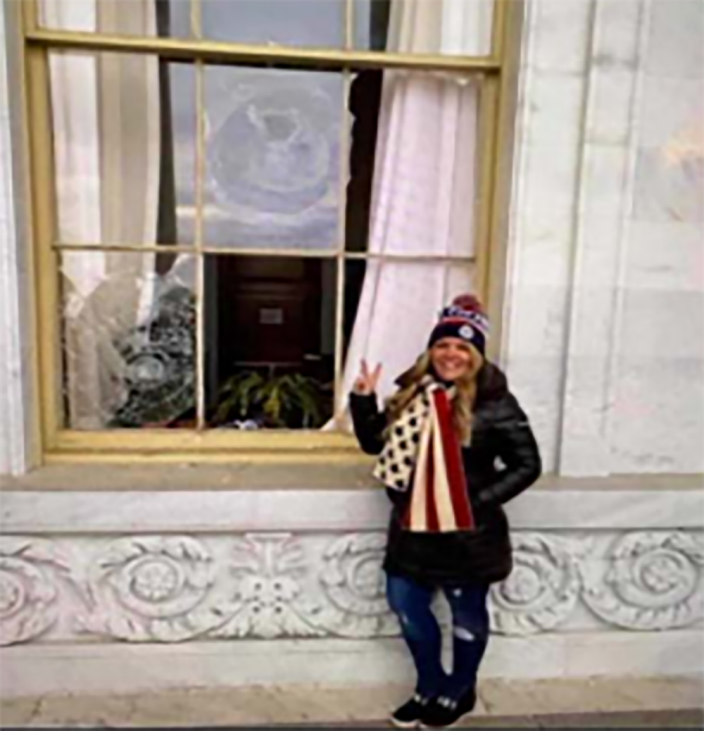 Image: Jenna Ryan in front of a broken window at the U.S. Capitol building. (U.S. Attorney's Office)