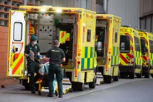 A line of four ambulances can be seen, with healthcare workers dealing with a patient in the ambulance at the front of the line