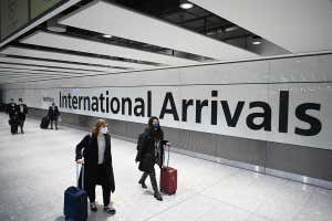 Passengers wearing face masks wheel suitcases through an airport terminal, past a large sign that reads: 'International Arrivals'