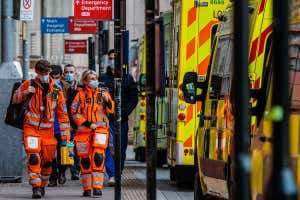 Workers wearing protective clothing walk next to a queue of ambulances outside the Royal London Hospital