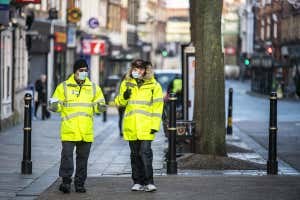 Two covid-19 advisors wearing high-visibility jackets patrol an empty High Street in Worcester city centre, England
