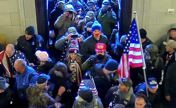 Image: Jenna Ryan, center, looking at her phone while entering the Capitol on Jan. 6, 2021. (U.S. Attorney's Office)