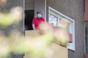 A woman wearing a face mask stands on a balcony in a retirement home