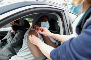 A person wearing a face mask leans out of a car window to get vaccinated