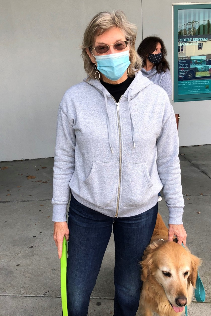 A woman in a mask stands with her golden retriever.