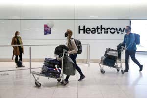 Passengers push luggage on trolleys through a terminal at London's Heathrow airport