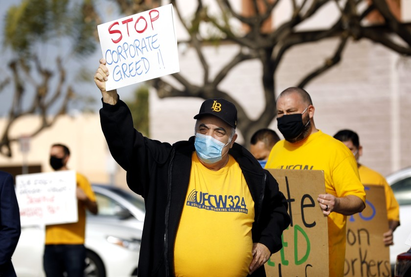 """A man holds a sign that says, """"Stop Corporate Greed' during a protest at a grocery store."""