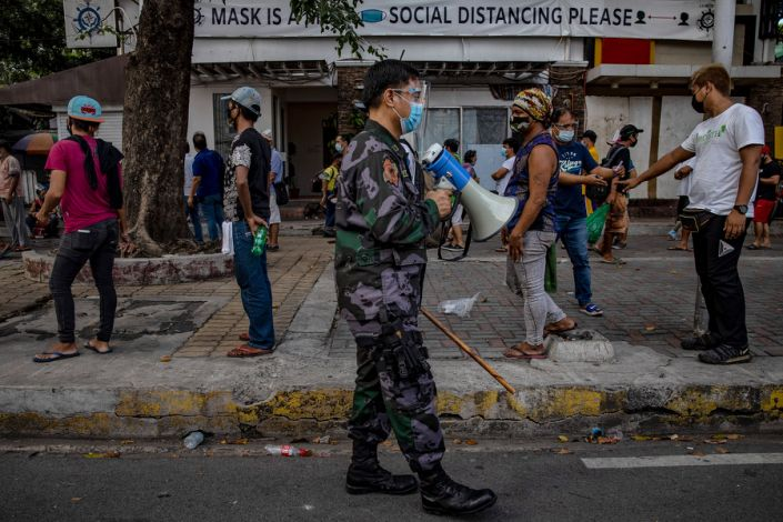 """A police officer reminds homeless people to practice social distancing as they queue to receive free meals distributed by members of the Society of the Divine Word (SVD) on Dec. 15, 2020 in Manila.<span class=""""copyright"""">Ezra Acayan—Getty Images</span>"""