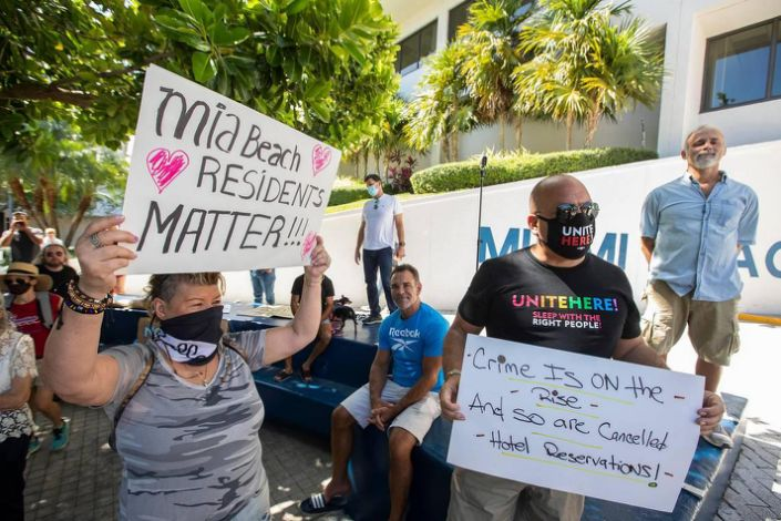 (L) Helena Velasquez holds a sign when Miami Beach residents gathered outside City Hall to protest how the city's handling of spring break, Saturday March 27th., 2021.