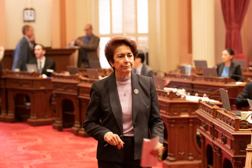 Anna Caballero walks across the floor of the California Senate.