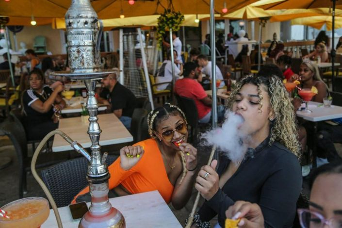 Spring breakers Karsyn Mcleod, 21, and Zayasha Fowler, 21, sit at a hookah bar and lounge on Ocean Drive in South Beach on Thursday, March 12, 2021.