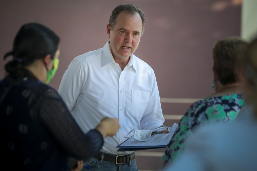 Adam Schiff holds a clipboard and speaks with women.