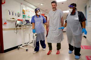 Two members of staff wearing personal protective equipment at King's College Hospital in London assist a patient recovering from covid-19 with walking